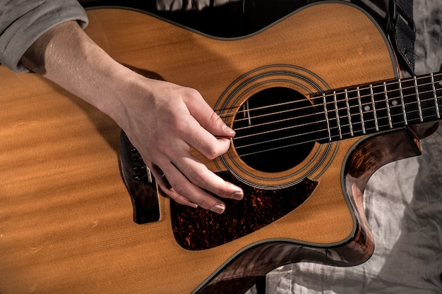 Gitarist, muziek. jonge man speelt een akoestische gitaar op een zwarte geïsoleerd Gratis Foto