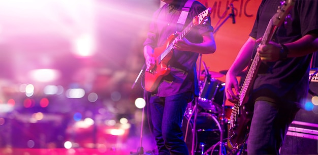 Gitaristen met kleurrijke verlichting op een podium Premium Foto