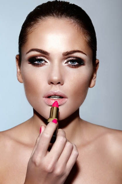 Glamour close-up portret van mooie sexy blanke brunette jonge vrouw model make-up lippenstift op haar lippen met perfecte schone huid toe te passen Gratis Foto