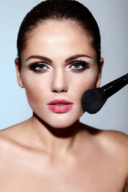 Glamour close-up portret van mooie sexy blanke brunette jonge vrouw model met perfecte schone huid make-up op haar gezicht toe te passen Gratis Foto