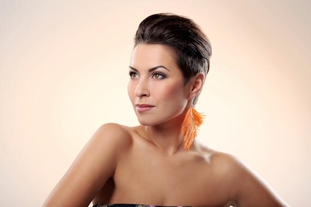 Glamour en prachtige brunette met veren oorbel Gratis Foto