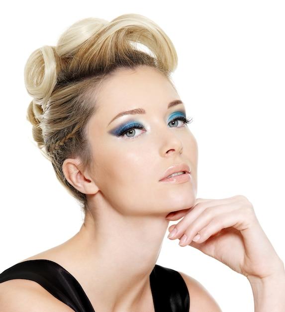 Glamour jonge vrouw met blauwe oogsamenstelling en krullend kapsel op witte ruimte Gratis Foto