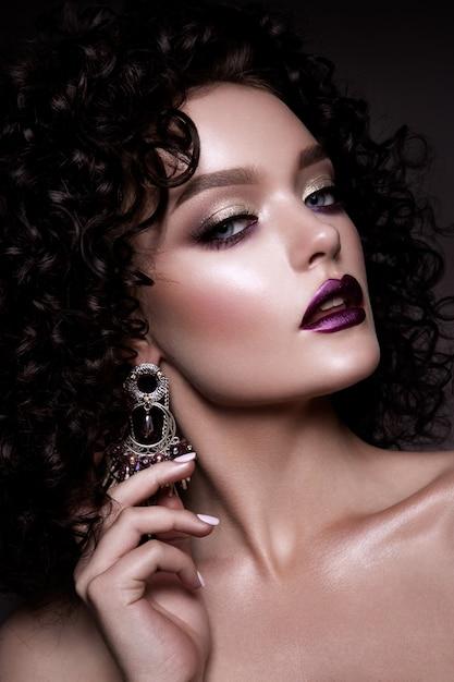 Glamourdame, mooi meisje op grijze achtergrond. portret. golvend haar, perfecte make-up. gesloten ogen. Premium Foto