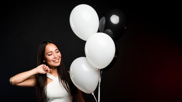 Glamoureuze vrouw poseren met ballonnen op feestje Gratis Foto