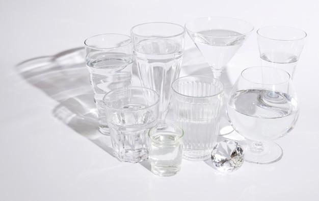 Glanzende diamant met glazen water op witte achtergrond Gratis Foto