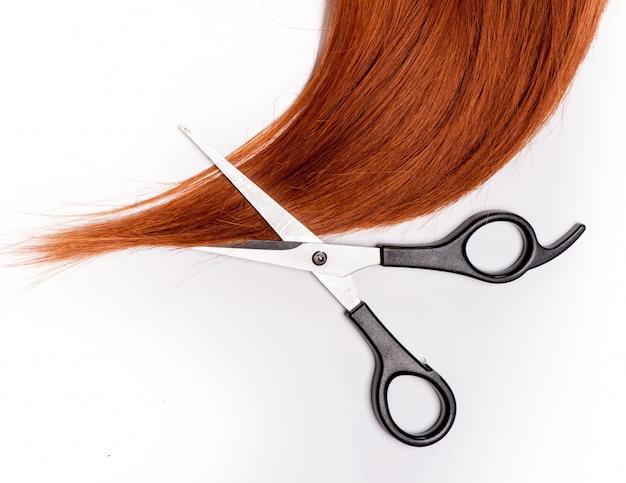 Glanzende rode haar en haar scherpe die scharen op wit worden geïsoleerd Premium Foto