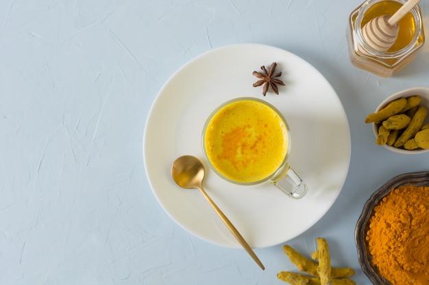 Glas ayurvedische gouden kurkuma latte melk met kurkuma poeder op wit. Premium Foto