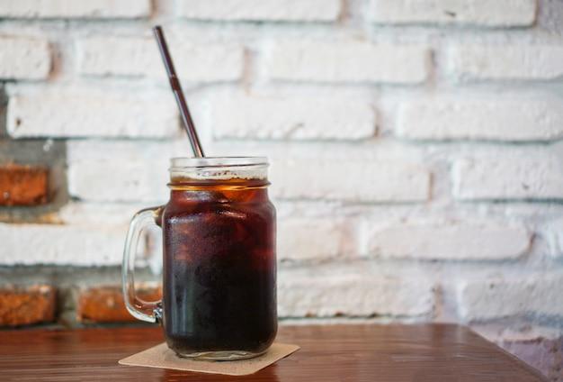 Glas bevroren zwarte koffie in kruik op de houten lijst met muurbaksteen Premium Foto