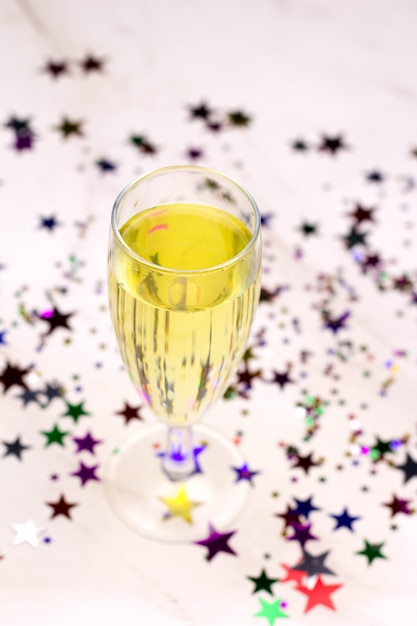 Glas champagne en confetti in de vorm van sterren, bovenaanzicht, wazig Premium Foto