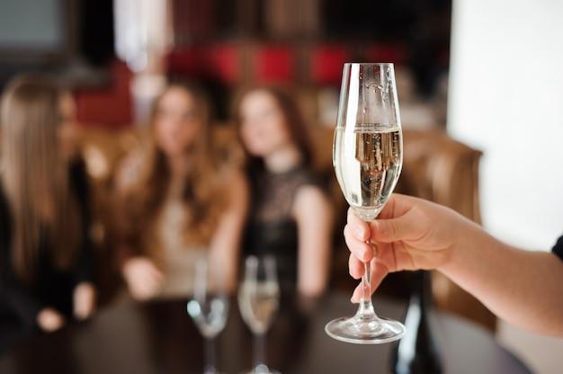 Glas champagne op de achtergrond van vrienden op een feestje Premium Foto