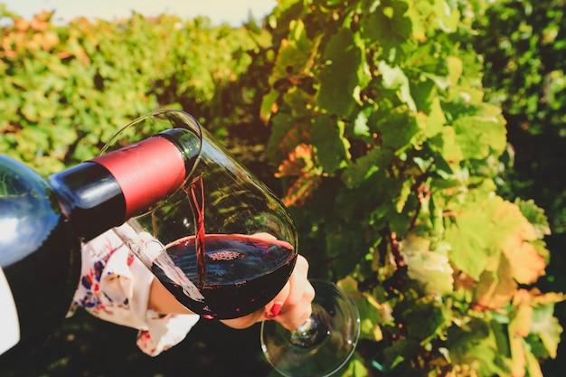 Glas en fles rode wijn in selectieve focus op glas wijn gieten rode wijn Premium Foto