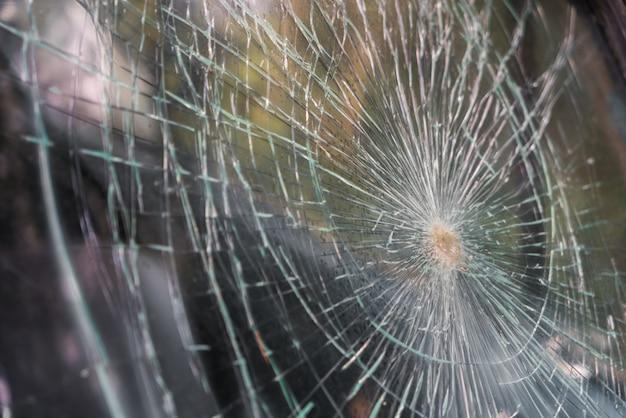 Glas gebroken barsten splinters in de voorkant van de auto. (Gefilterde afbeelding Gratis Foto