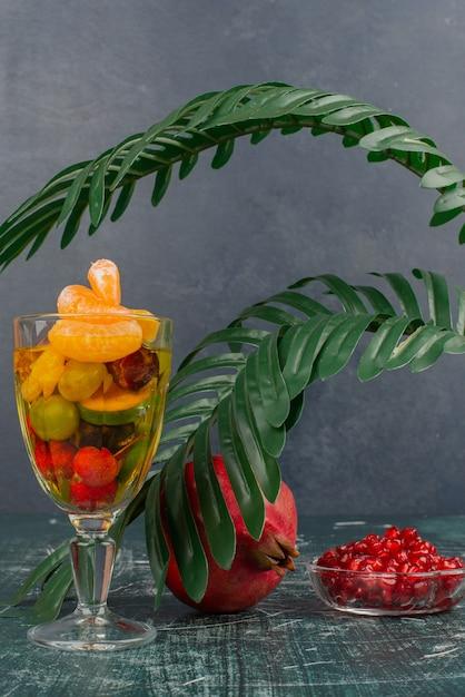 Glas gemengd fruit en granaatappel met zaden op marmeren tafel. Gratis Foto