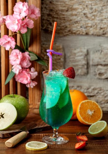 Glas groene cocktail met appelplakken, ijs en aardbei Gratis Foto