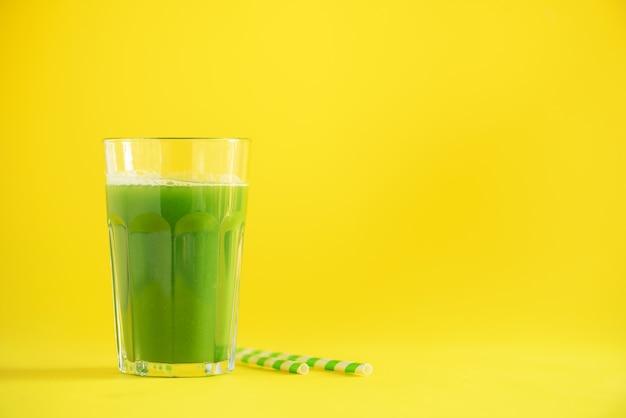 Glas groene selderiesmoothie op gele achtergrond Premium Foto