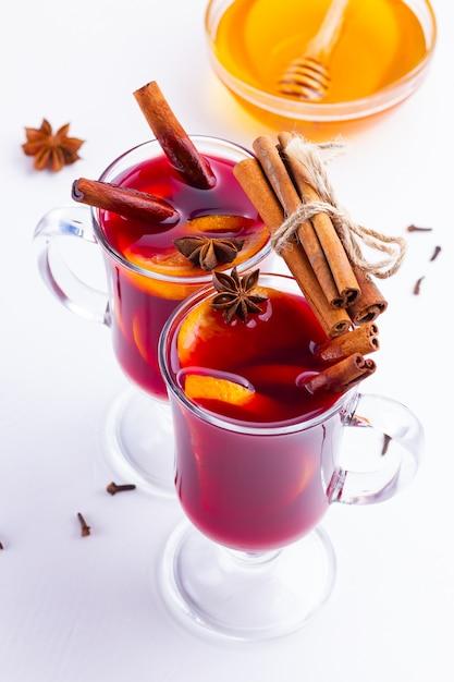 Glas hete glühwein met kruiden en honing op witte achtergrond Premium Foto