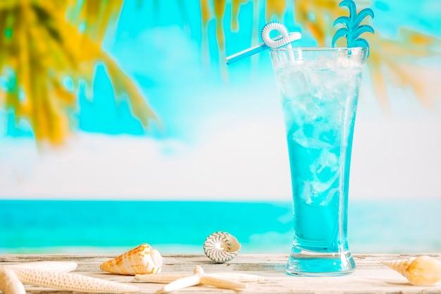 Glas koelende blauwe drank en zeesterren Gratis Foto