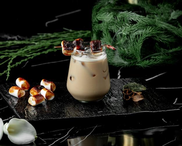 Glas koffie drinken met ijs gegarneerd met geroosterde marshmallow Gratis Foto