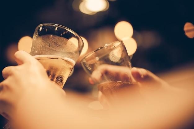 Glas koud bier bodems met prachtige bokeh, vrienden drinken bier samen, donkere toon Premium Foto