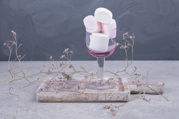 Glas marshmallows op een houten bord met plant. hoge kwaliteit foto Gratis Foto