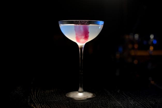 Glas met een roze ijsblokje en een lichtblauwe cocktail die zich in de bar bevindt Premium Foto