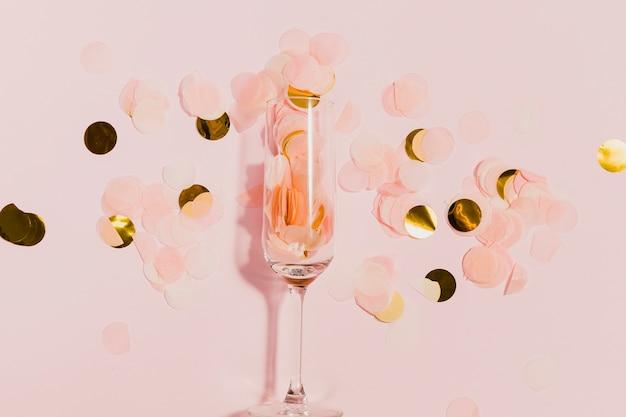 Glas met gouden confetti op nieuwjaarsfeest Gratis Foto