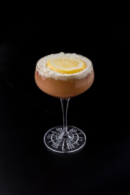 Glas met rode cocktail met room en oranje plak op zwarte achtergrond Premium Foto