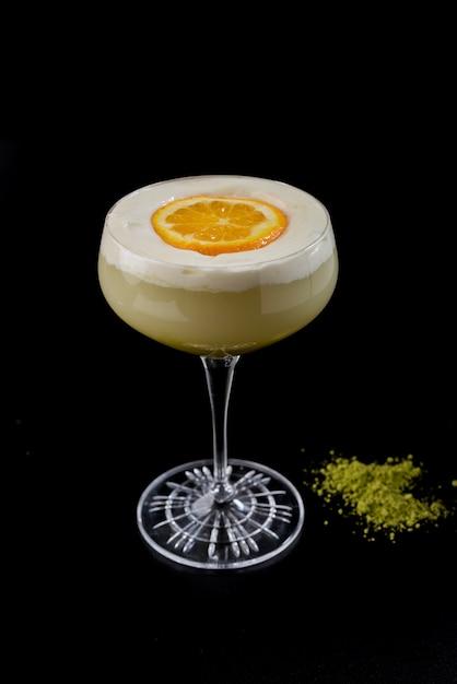 Glas met romige cocktail met room en oranje plak en wasabi op zwarte achtergrond Premium Foto