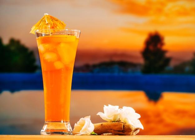Glas oranje drankje en witte bloemen Gratis Foto