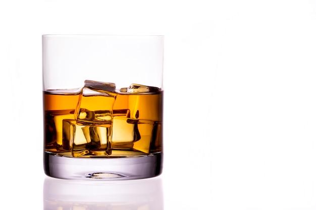 Glas schotse whisky en ijs op een witte achtergrond Premium Foto