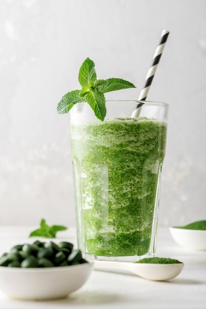 Glas smoothies met toevoeging van chlorella of spirulina met munt op een grijze betonnen achtergrond. Premium Foto