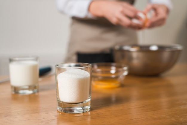 Glas suiker op de voorgrond met vervaging vrouw breken ei in de kom Gratis Foto