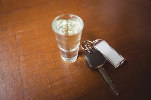Glas tequilaschot met autosleutel in barteller Gratis Foto