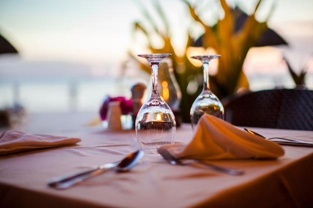 Glas van de close-up het lege wijn op de gedekte lijst bij zonsondergang Premium Foto