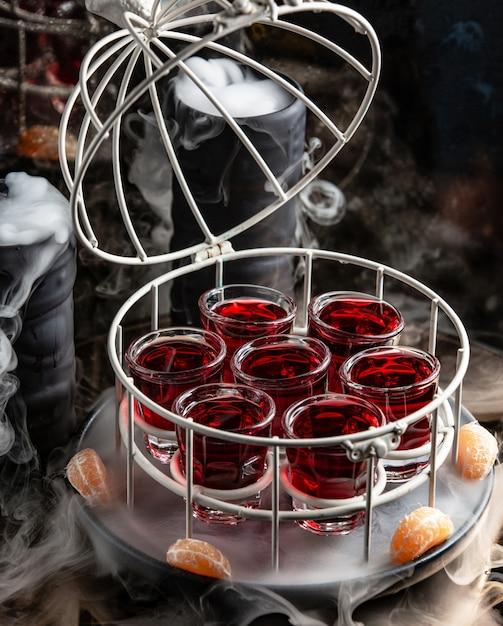 Glas van rood schot dat in kooi met open bovenkant in gerookte pot wordt gediend Gratis Foto