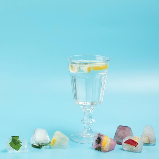 Glas water met citroen met ijsblokjes op blauwe backgrounes Gratis Foto