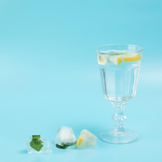 Glas water met citroen op blauwe achtergrond Gratis Foto