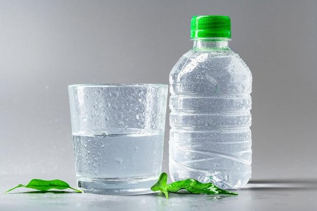 Glas water met een fles op tafel Premium Foto