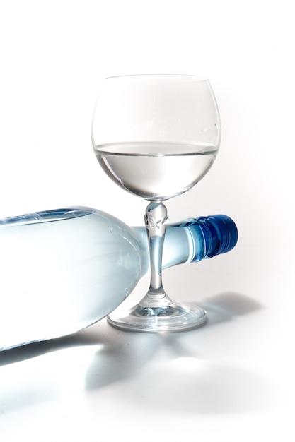 Glas water met een geïsoleerde fles Premium Foto