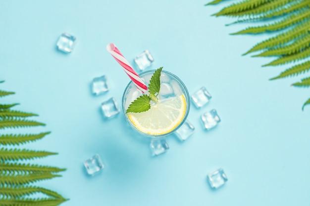Glas water of drankje met ijs, citroen en mint op een blauwe ondergrond met palmbladeren en varens. ijsblokje. concept van de hete zomer, alcohol, koel drankje, dorst lessen, bar. plat lag, bovenaanzicht Premium Foto
