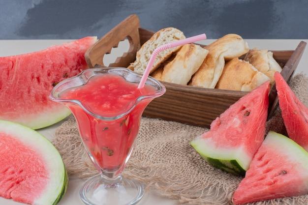 Glas watermeloen smoothie en mandje brood op witte tafel. Gratis Foto