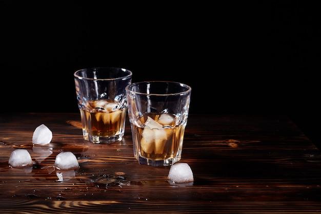 Glas whisky met rook en ijs op een houten tafel Premium Foto