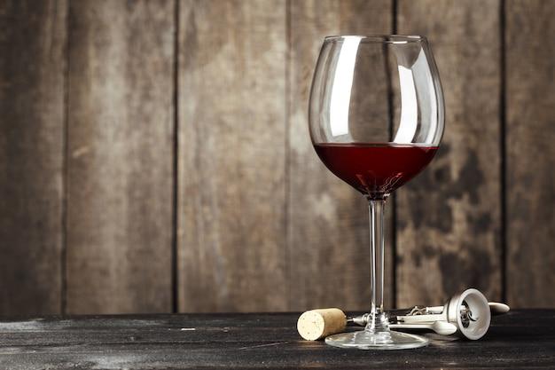 Glas wijn op de houten tafel Premium Foto