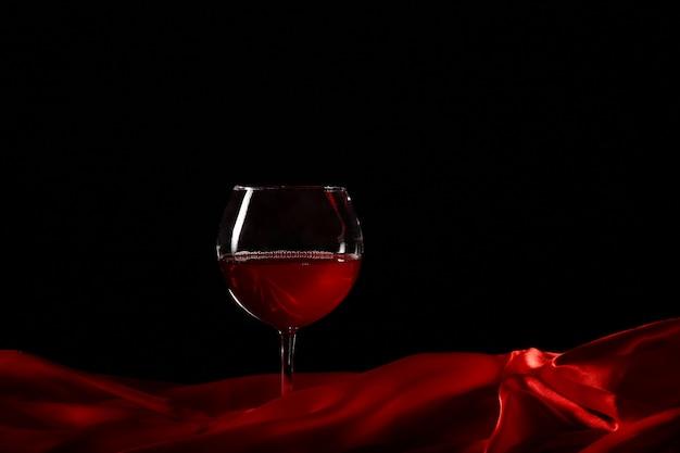 Glas wijn op rode zijde met donkere achtergrond Premium Foto