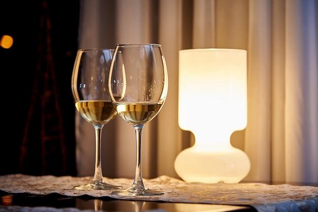Glas witte wijn op tafel met een brandende lamp in een gezellig restaurant. Premium Foto