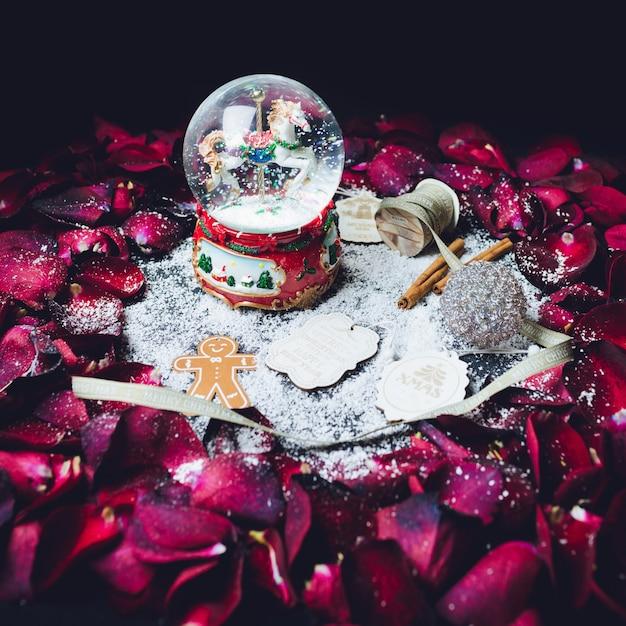 Glasbal met sneeuw en andere kerstversiering staat in de cirkel van rode rozenblaadjes Gratis Foto