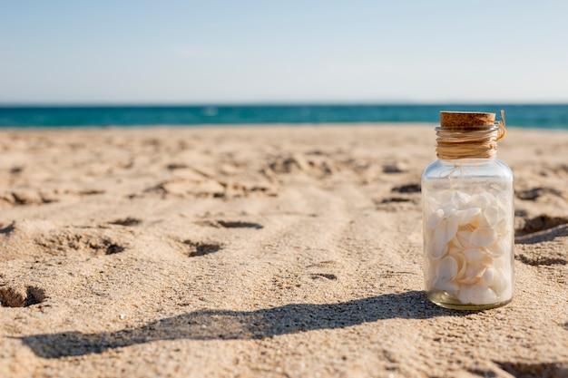 Glasfles met zeeschelpen op zand Gratis Foto