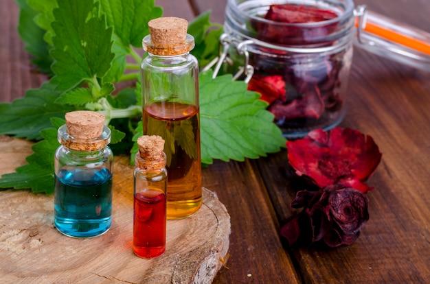 Glasflessen aromaetherische olie op houten, beeld voor alternatieve therapiegeneeskunde Premium Foto