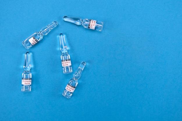 Glazen ampullen met kant-en-klaar covid19-vaccin liggen op blauw, blanco met ruimte voor tekstweergave van bovenaf Premium Foto