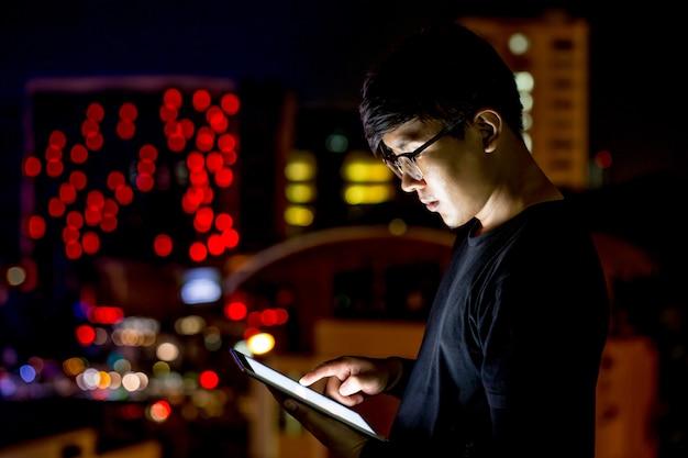 Glazen aziatische man kijkt naar zijn computer tablet tijdens de nacht met stadslichten. focus op zijn hand. ondiepe scherptediepte. Premium Foto